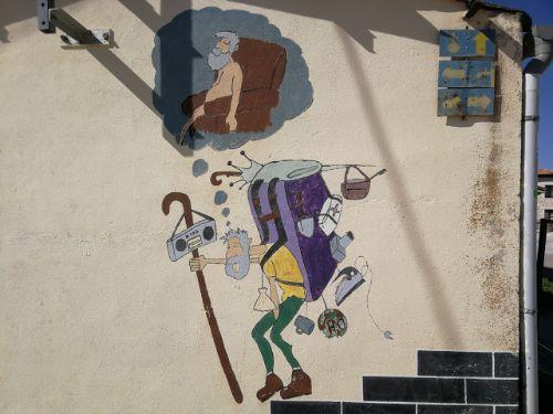 Jakobsweg Graffiti: Ein Pilger schleppt einen schweren Rucksack.